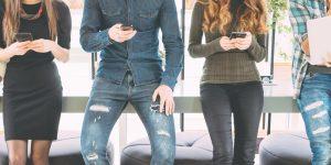 Junge Leute mit Smartphone auf Bank